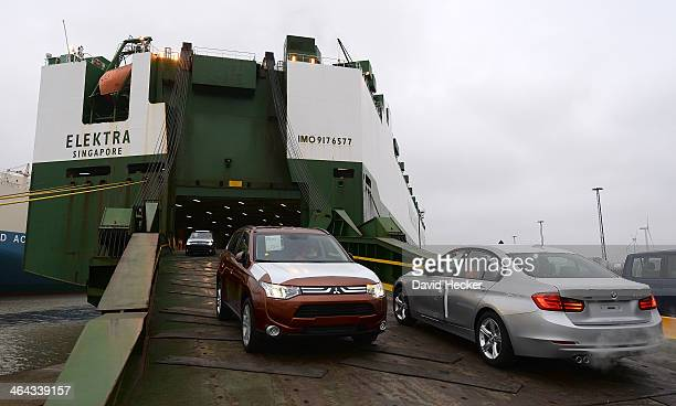 BMW car destined for export overseas is loaded onto ship on January 22 2014 in Bremerhaven Germany while Mitsubishi car produced in Japan is leaving...