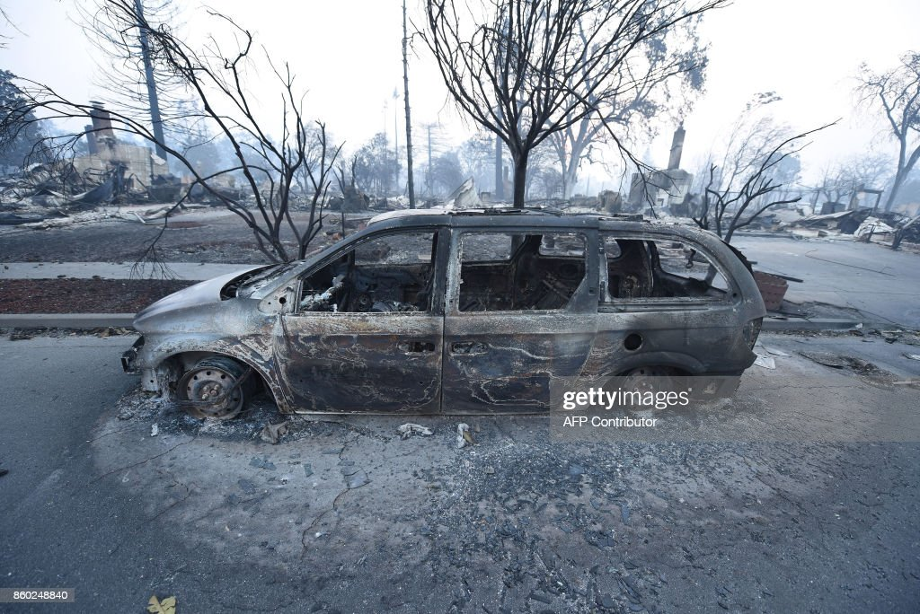 A car destroyed by wildfires is seen in Santa Rosa, California, on October 11, 2017. The toll from Northern California's ranging wildfires continued to grow as officials said the fires destroyed up to 2,000 structures and killed at least 17 people. / AFP PHOTO / Robyn Beck