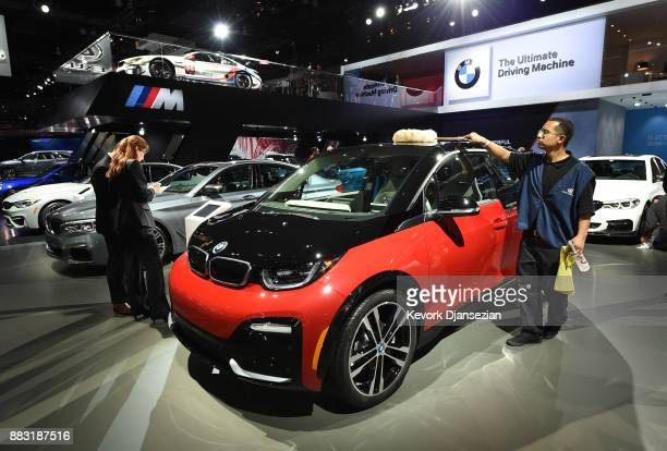 A car detailer dusts off the 2018 BMW i3s electric car during the auto trade show AutoMobility LA at the Los Angeles Convention Center November 30 in...