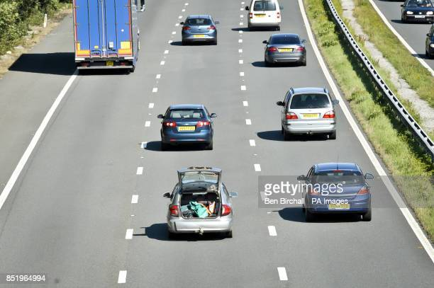 A car dirves with its boot open on the M5 Motorway near Bridgend Wales