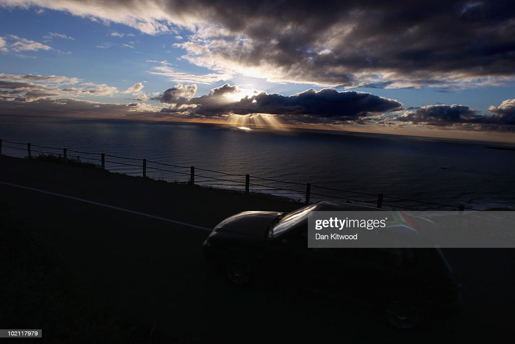 A car displaying a South African Flag drives to Signal Hill at sunset on June 15, 2010 in Cape Town, South Africa.