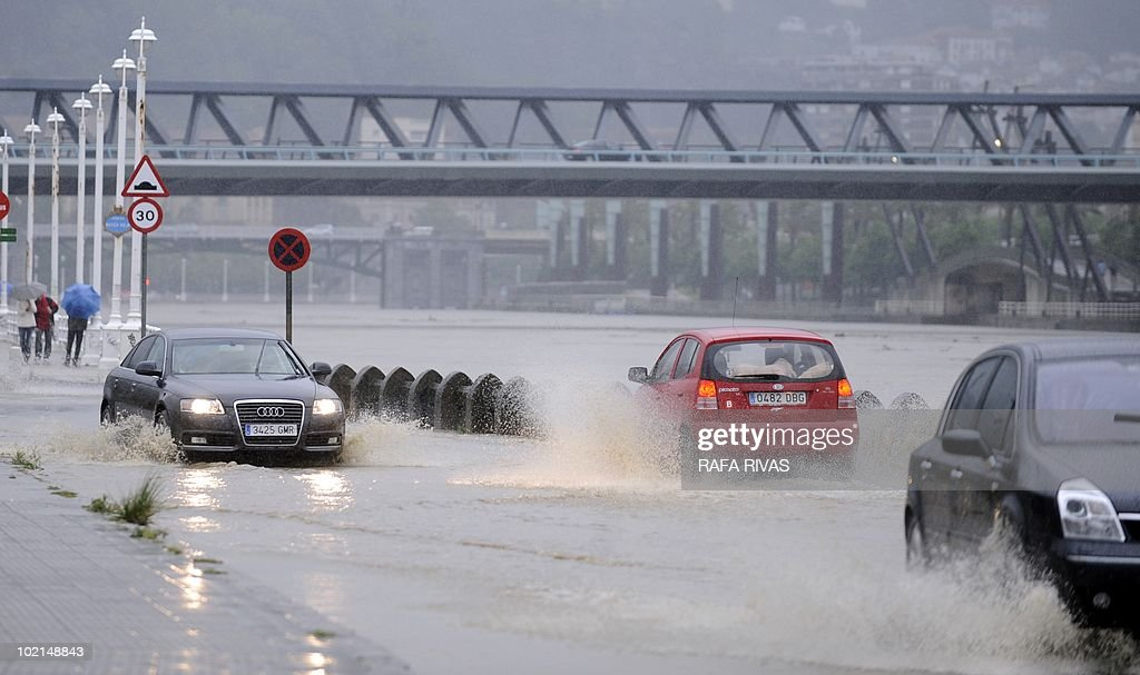 Car drive on a flooded road along the Nervion river after heavy rains in the northern Spanish Basque city of Bilbao on June 16, 2010. AFP PHOTO/Rafa Rivas