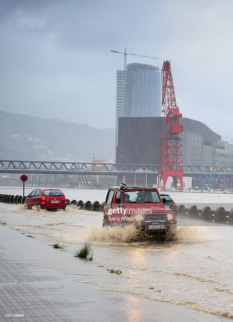Car drive on a flooded road along the Nervion river after heavy rains in the northern Spanish Basque city of Bilbao on June 16, 2010. AFP PHOTO / Rafa Rivas