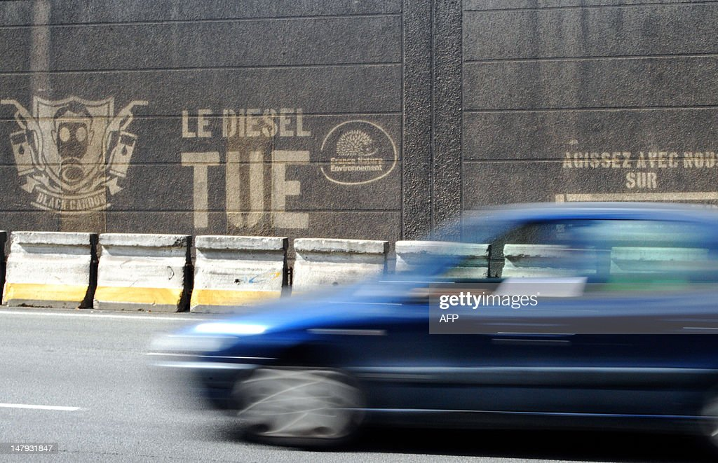 A car drive on the banks of the Seine river in Paris on July 6, 2012, pasts graffiti on a wall, reading 'Diesel Kills,' as part of a series of events by militant group France Nature Environnement to raise public awareness about the dangers of diesel fumes and their impact on people.