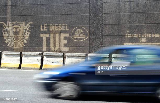 A car drive on the banks of the Seine river in Paris on July 6 pasts graffiti on a wall reading 'Diesel Kills' as part of a series of events by...