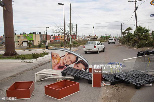 Car drive past debris after looting in Veracruz City Mexico on Saturday Jan 7 2017 Mexico's National Association Of Retail And Department Stores says...