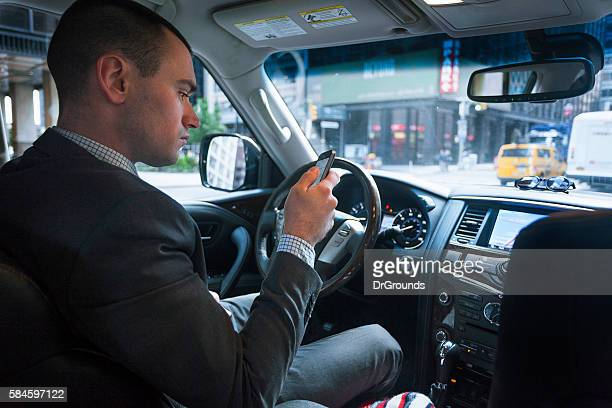 Car driver checking phone