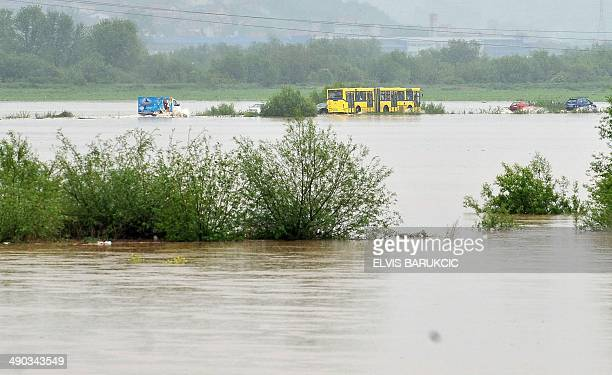 Car drivers drive alonga flooded road in Sarajevo's Western suburb of Doglodi as the river Bosna has floodedthe surrounding area after heavy rainfall...