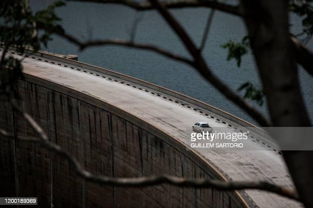 Car drives across the Kariba Dam towards the Zimbabwean border, in Kariba on January 20, 2020. - In the absence of sufficient rain, the Kariba dam,...