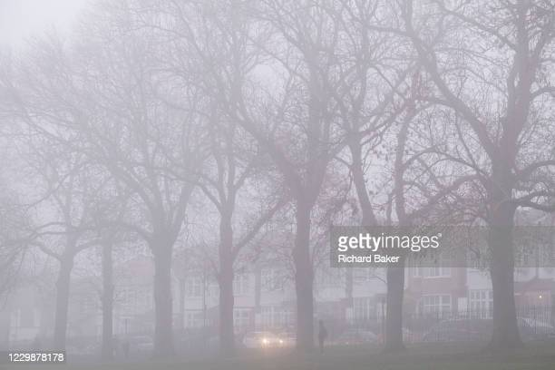 Car drives along a residential street with its headlights on to see through early morning mist, on 27th November 2020, in London, England.