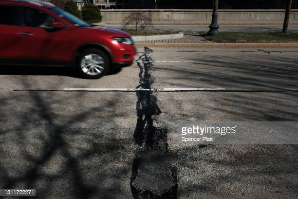 Car drives along a road in need of repair on April 09, 2021 in Providence, Rhode Island. Rhode Island consistently ranks as one of the worst states...