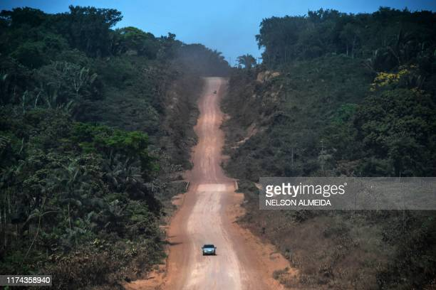 A car drives along a section under construction of the TransAmazonian highway near Ruropolis Para state Brazil in the Amazon rainforest on September...