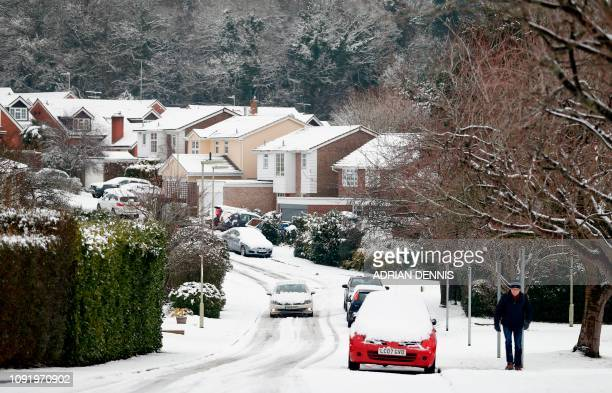 A car drives along a snowcovered residential road in Hartley Wintney in Hampshire 40 miles west of London on February 1 2019 Snowfall and icy...