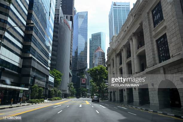 Car drives along an otherwise empty road in the financial district of Singapore on April 24 as the country undergoes a partial lockdown to fight the...