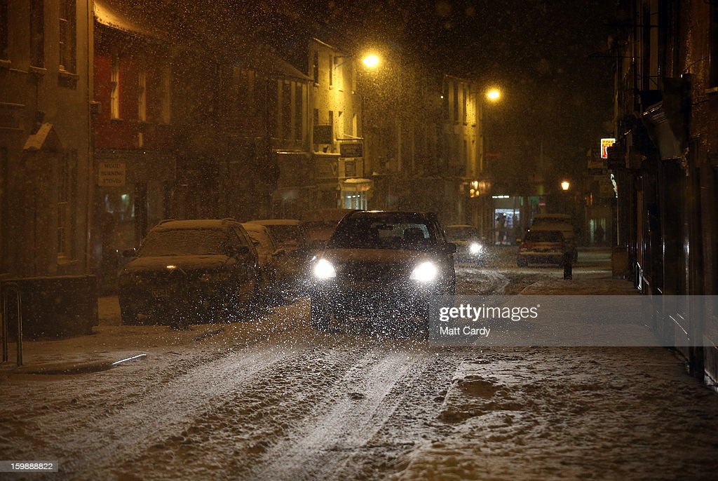 A car drives along Shepton Mallet high street on January 22, 2013 in Somerset, England. Fresh snow has brought fresh disruption to parts of the UK.