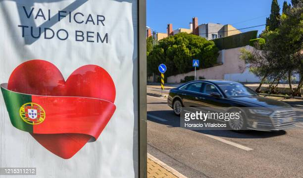 A car drives by a bus stop advertising panel reading All Be Well sponsored by Swatch showing a heart wrapped in the Portuguese flag during COVID19...