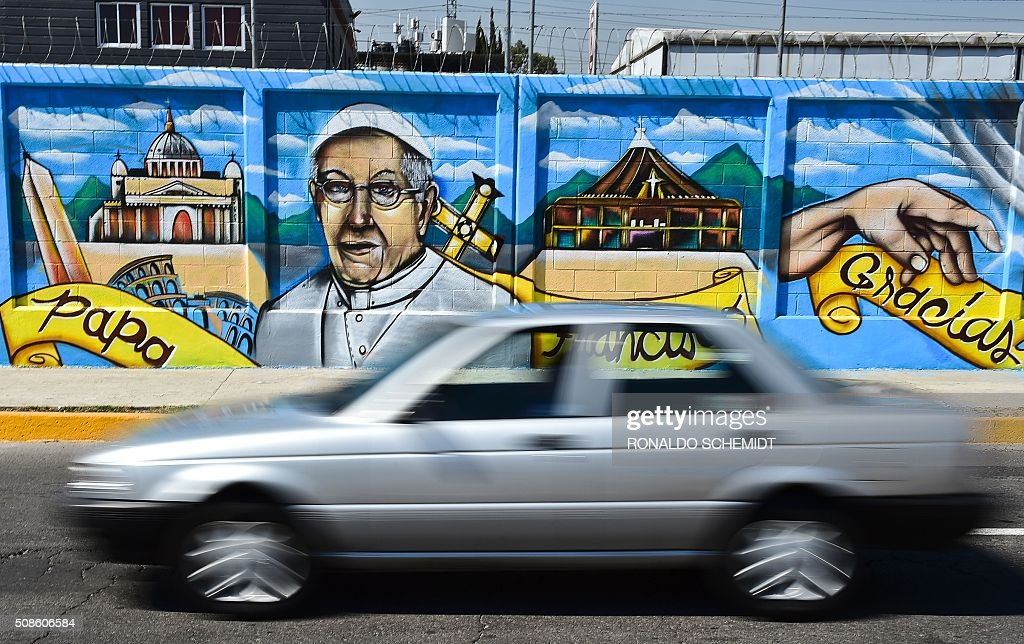 A car drives by a mural welcoming Pope Francis to Ecatepec, on the north east side of Mexico City, on February 5, 2016. The Pope will visit Mexico February 12-17.