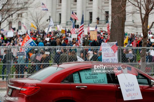 A car drives by as protesters against the coronavirus shutdown gather in front of the State Capitol in Madison Wisconsin on April 24 2020 Gyms hair...