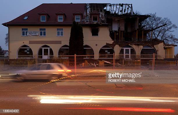 A car drives by at the burnt house of selfconfessed neoNazi 36yearold woman Beate Z as dusk sets in Zwickau eastern Germany on November 16 2011 Beate...