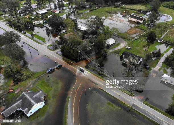 A car drives down a flooded road on September 16 2018 in Leland North Carolina The state is experiencing wide spread flooding after Hurricane...