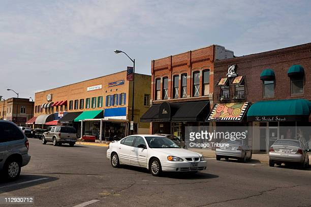 Car drives down North 2nd Avenue past small boutique shops and a coffee house in downtown Newton, Iowa, September 9, 2007. The small community of...