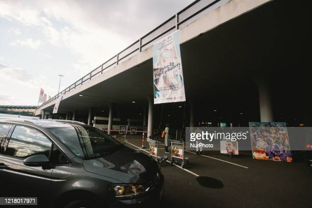 A car drives into the gallery show during the opening of drive in Gallery's show Nachtbroetchen 20 at Cologne airport parking lot amid the...