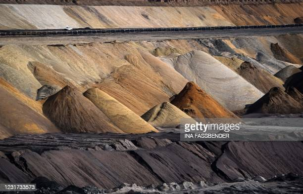 Car drives near the open-cast mine of German energy giant RWE in Garzweiler, western Germany, on March 15, 2021. - On March 16 the group will present...