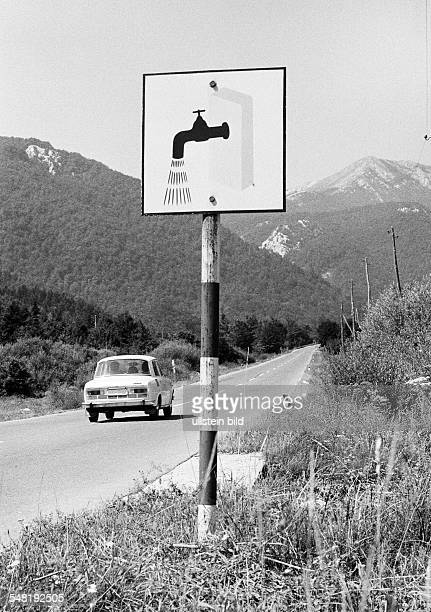 car drives on a country road through the Velebit mountains a signboard at the roadside leads to the next resting place with washing option Croatia at...