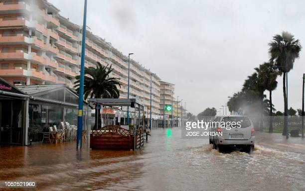 A car drives on a flooded street in Peniscola on October 19 during heavy rains that hit eastern Spain
