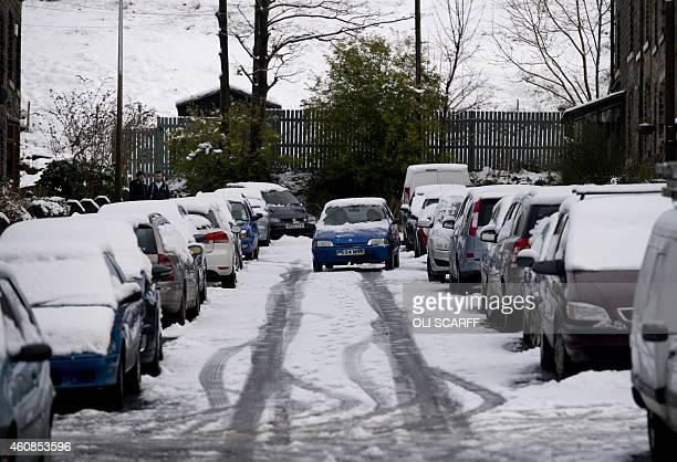 A car drives on an untreated road in the village of Marsden northern England on December 27 2014 Overnight flurries left parts of Britain blanketed...