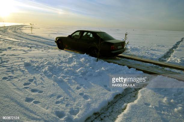 A car drives on February 17 2011 on a wooden crossing built to pass cracks in the ice on Estonia's longest ice road in Europe The 265 kms road in...