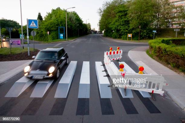 A car drives over an apparent threedimensional crosswalk painted on a street at the Walperloh district of Schmalkalden central Germany on May 5 2018...