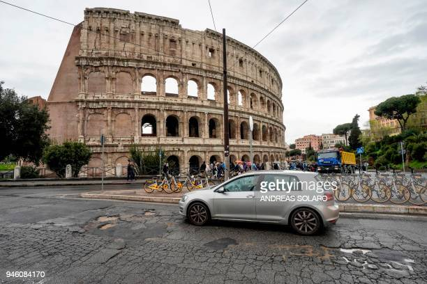 A car drives over potholes on a road past the Colosseum in downtown Rome on April 12 2018 Romes roads problems have been existing for years due to...