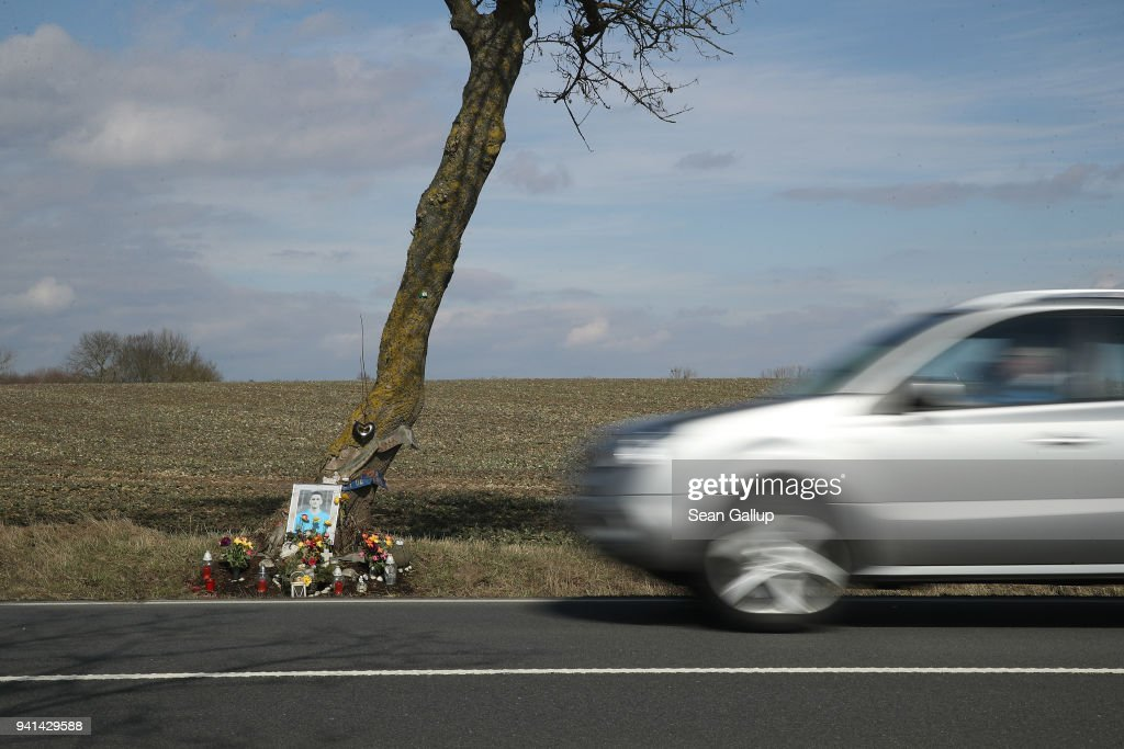 A car drives past a country road-side memorial to a young