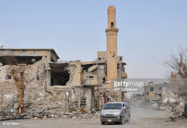 A car drives past a damaged mosque in the eastern Syrian city of Deir Ezzor during a military operation by government forces against Islamic State...