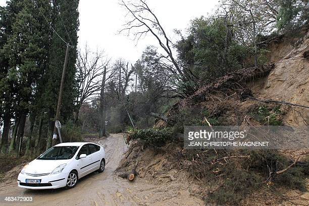 A car drives past a landslide in SainteAgnès southeastern France on January 18 2014 Many roads have been cut in the AlpesMaritimes due to landslides...