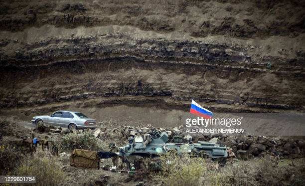 TOPSHOT A car drives past a Russian peacekeepers' checkpoint outside the town of Shusha on November 13 during a ceasefire in the military conflict...
