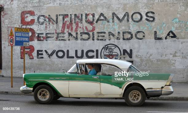 TOPSHOT A car drives past a wall reading 'We Continue Defending Revolution' referring to Committees for the Defense of the Revolution in Havana on...
