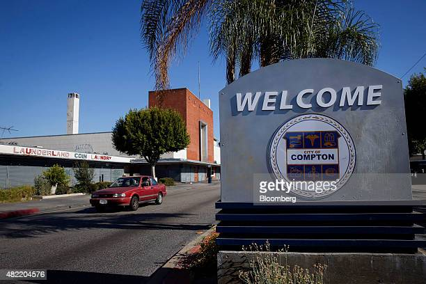 A car drives past a Welcome to Compton sign in Compton California US on Friday June 19 2015 It can be a letdown for LA Hood Life Hip Hop Tours...