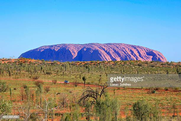 A car drives past Ayers Rock or Uluru on December 29 2008 in Northern Territory Australia