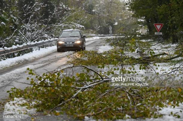 A car drives past broken branches near TournonsurRhone on November 15 after snow fall France's weather service placed 11 departments in the south...