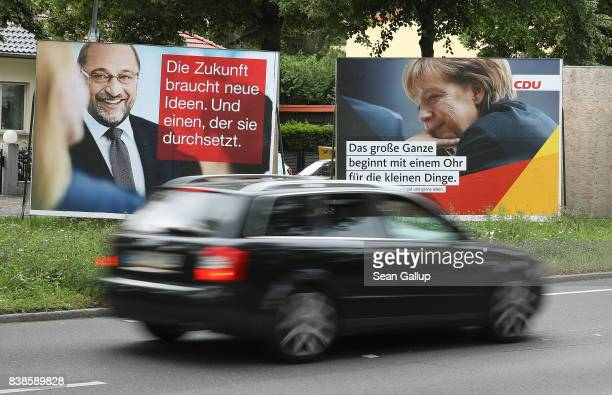 A car drives past election campaign billboards that depict German Social Democrat and chancellor candidate Martin Schulz and German Chancellor and...