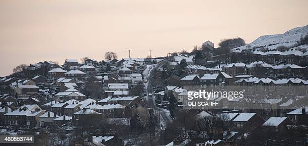 A car drives past snowcovered houses in the village of Marsden northern England on December 27 2014 Overnight flurries left parts of Britain...
