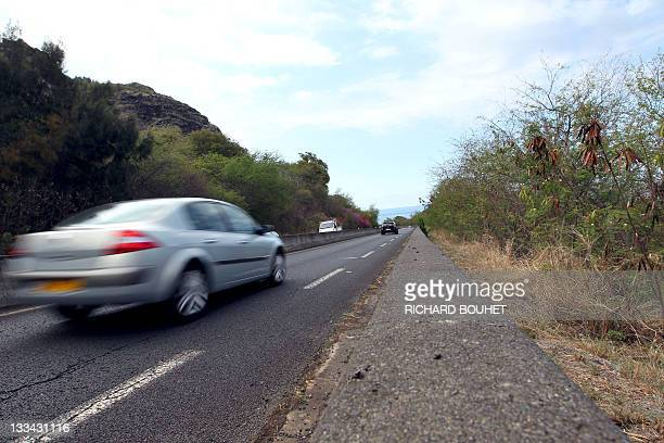 A car drives past the place where the dead body of British security agent Carl Davies was found last November 9 near SaintDenis de la Réunion on the...