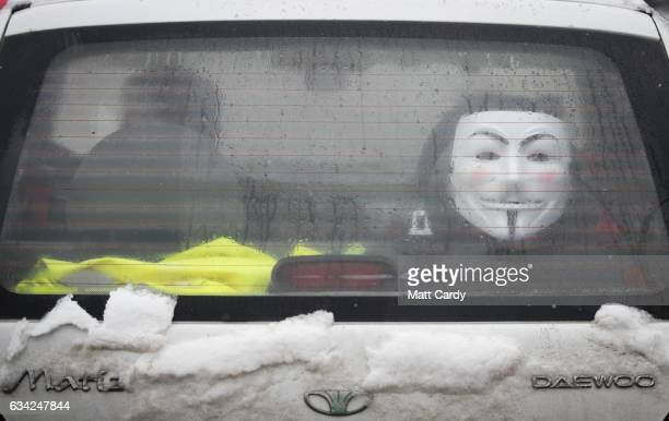A car drives past with a Guy Fawkes mask displayed in the rear window in central Bucharest on February 8 2017 in Bucharest Romania Romania's ruling...