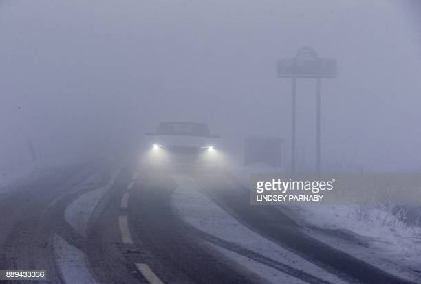 A car drives slowly through the fog and snow on one of the rural roads in Derbyshire northern England on December 10 2017 The heaviest snowfall to...