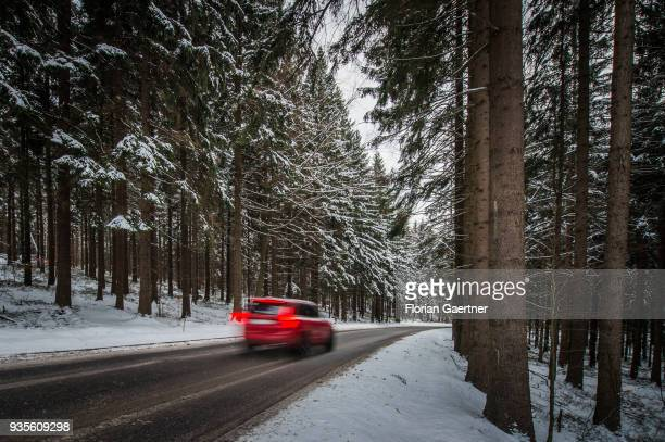 A car drives through a conifer forest at winter on March 17 2018 in Liberec Czech Republic