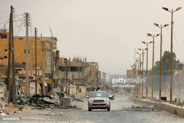 A car drives through a damaged street on the outskirts of Deir Ezzor on September 24 as Syrian government forces continue to press forward with...