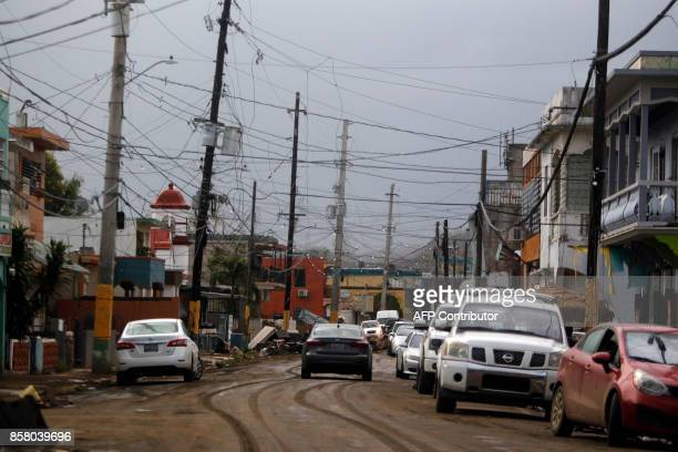 A car drives through a dry mud covered street after the area was affected by the passing of Hurricane Maria in Toa Baja Puerto Rico on October 5 2017...