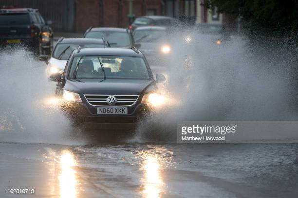 A car drives through a flooded road on August 16 2019 in Pontypridd Wales The Met Office have issued a yellow weather warning for rain for Wales and...
